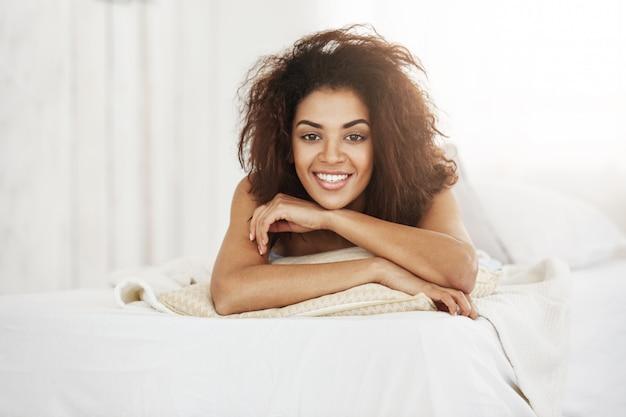 自宅の枕の上に横たわる美しい幸せなアフリカ女笑顔します。