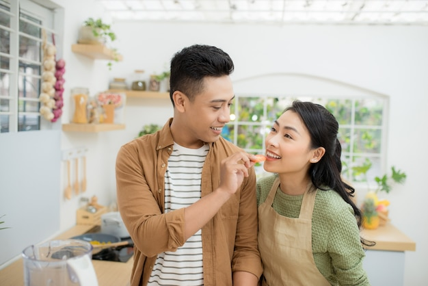 아름다운 행복한 아시아 커플이 부엌에서 서로에게 먹이를 주고 있습니다.