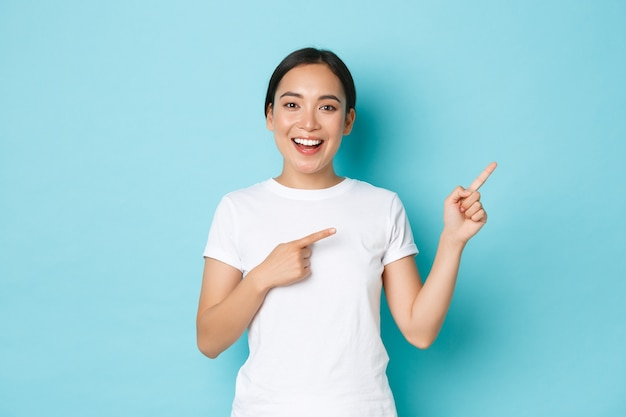 Beautiful happy asian girl in white t-shirt helping with choice, showing way or demonstrating. korean woman looking enthusiastic while pointing upper right corner over blue wall