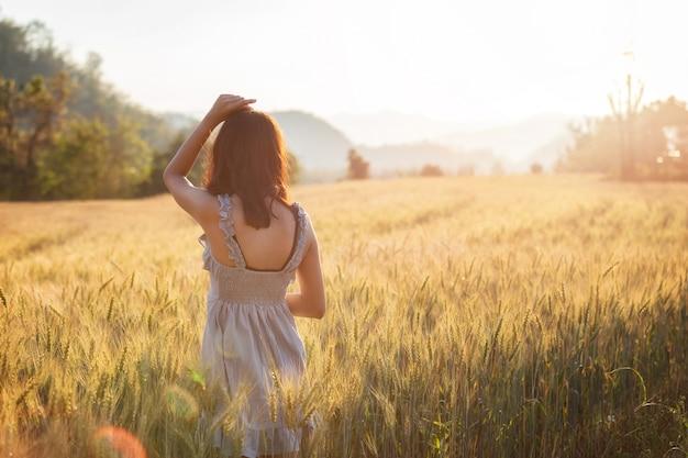 Beautiful and happy asian woman enjoying life in barley field at sunset.