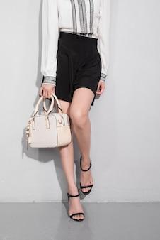 灰色の背景の上に立っているバッグを保持している美しい幸せなアジアの女性。