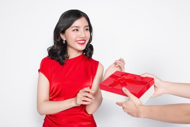 선물 상자를 받는 빨간 드레스에 아름 다운 행복 한 아시아 여자