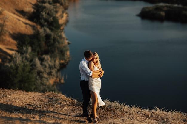 湖で抱き締める美しい幸せな新郎新婦。丘の上に立っている新郎と新婦の美しい若い結婚式のカップル