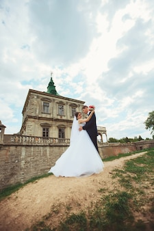 Beautiful happy bride and groom posing in a yard of medieval castle