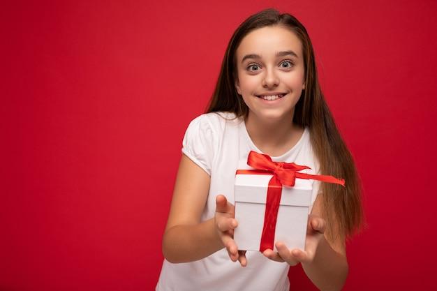 선물 상자를 들고 세련 된 캐주얼 옷을 입고 화려한 배경 벽 위에 절연 아름 다운 행복 갈색 머리 소녀