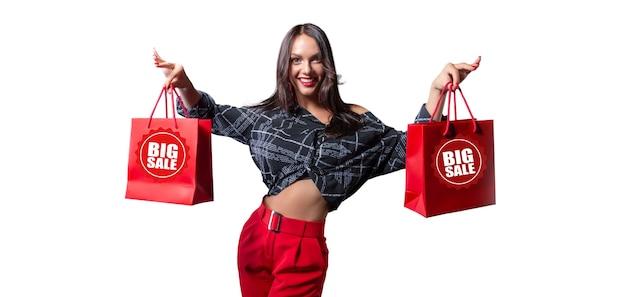 彼女の手に赤いパッケージを持つ美しい幸せなブルネット。白色の背景。割引、販売、購入のコンセプト。ミクストメディア