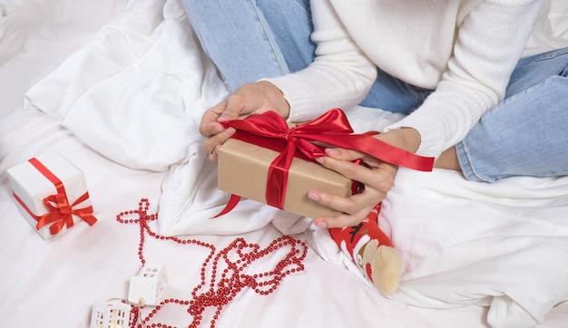 美しい幸せなブルネットの女性は白いセーターとクリスマスの帽子で電話で自分撮りをし、
