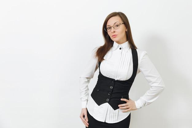 黒のスーツ、白いシャツ、白い背景で隔離のカメラを探しているメガネの美しい幸せな白人の若い笑顔の茶色の髪のビジネス女性。マネージャーまたは労働者。広告用のスペースをコピーします。