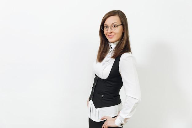 Красивая счастливая кавказская молодая усмехаясь бизнес-леди коричневых волос в черном костюме, белой рубашке и очках смотря камеру изолированную на белой предпосылке. менеджер или рабочий. скопируйте место для рекламы.