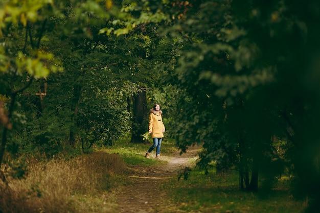 黄色のコート、ジーンズ、緑の森のブーツで美しい幸せな白人の若い笑顔の茶色の髪の女性。秋の黄金の葉が屋外の初秋の公園に立って歩いているファッション女性モデル。
