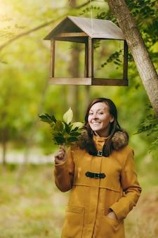 黄色のコート、ジーンズ、緑の森のブーツで美しい幸せな白人の若い笑顔の茶色の髪の女性。屋外の初秋の公園で鳥の餌箱の下に立っている紅葉のファッションモデル。