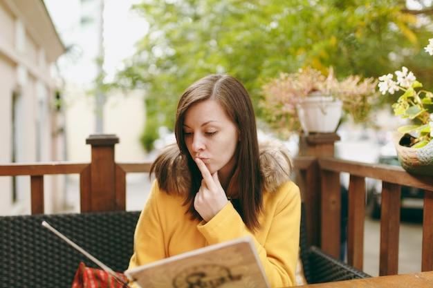 노란 코트를 입고 웃고 있는 아름다운 백인 젊은 여성, 도로 근처 야외 레스토랑이나 카페에서 메뉴를 주문하고 가을철 저녁에 무엇을 먹을지 결정합니다.