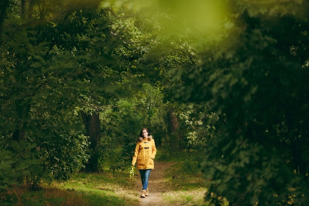Beautiful happy caucasian young smiling brown-hair woman in yellow coat, jeans, boots in green forest. fashion female model with fall golden leaves standing and walking in early autumn park outdoors.