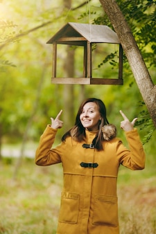 Beautiful happy caucasian young smiling brown-hair woman in yellow coat, jeans, boots in green forest. fashion model with fall leaves standing under bird feeders in early autumn park outdoors.