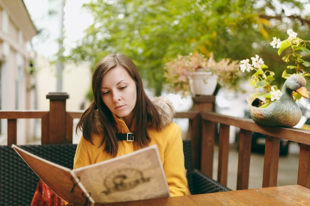 Beautiful happy caucasian young smiling brown-hair woman in yellow coat reading, ordering from menu in outdoor restaurant or cafe near road and deciding what to eat on dinner in autumn season.