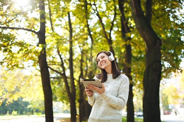 The beautiful happy cheerful brown-haired woman in white sweater with a tablet listening music in the white headphones in fall park on a warm day. autumn in the city.