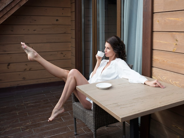 발코니에서 커피를 마시는 흰색 실크 가운을 입은 아름다운 행복한 쾌활한 갈색 머리 여자