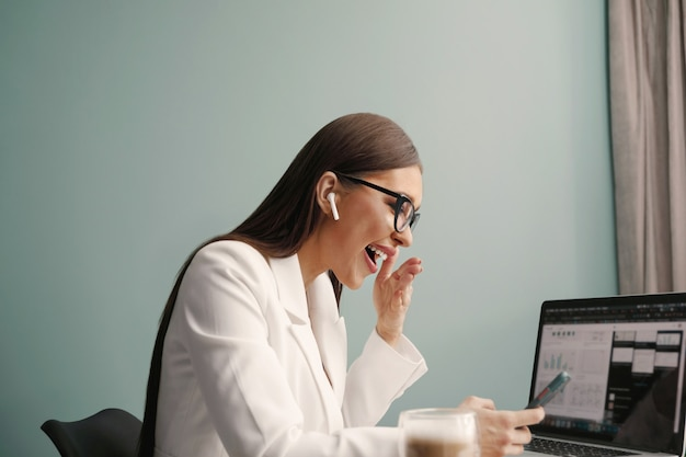Beautiful happy cheerful cute woman sit indoors in office using laptop computer and phone, listening music with earphones. businesswoman working on laptop.