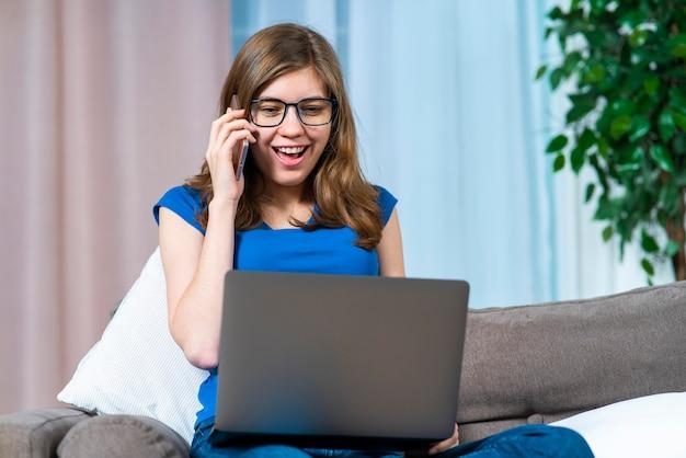 美しい幸せな陽気な女の子、眼鏡をかけた若い興奮したポジティブな女性は、彼女のラップトップコンピューターの画面を見て、自宅の携帯電話でソファやリビングルームのソファで話している。