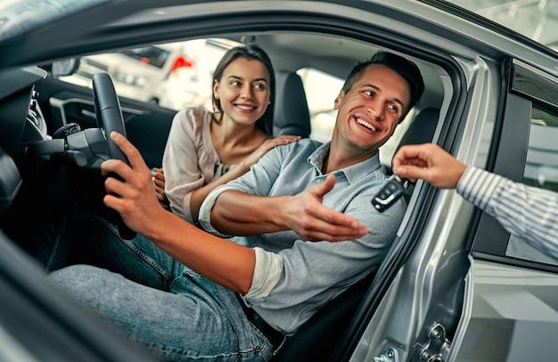 Красивая счастливая пара покупает машину в автосалоне и получает ключи от менеджера.
