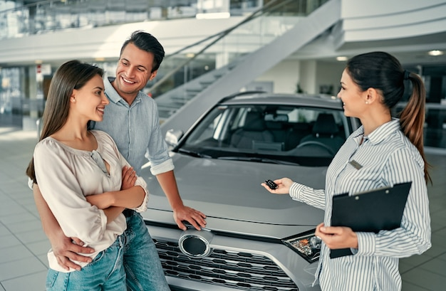Beautiful happy couple bought a car in the dealership and receives the keys from the manager.