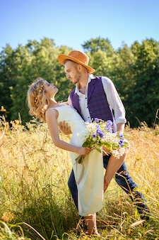 Beautiful happy couple dancing in a field in summer on a sunny day.