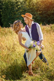 Beautiful happy couple dancing in a field in summer on