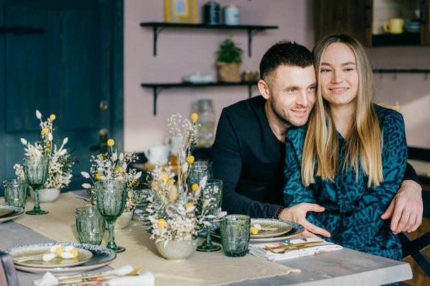 愛の美しい幸せなカップルは装飾されたテーブルで抱いています。