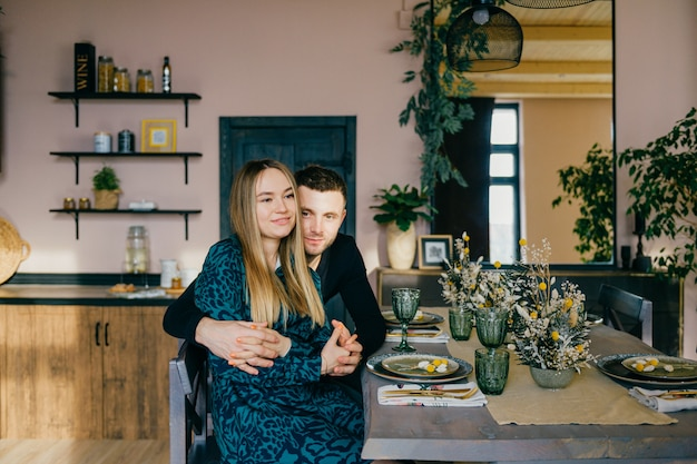 愛の美しい幸せなカップルは装飾されたスタジオで抱いています。