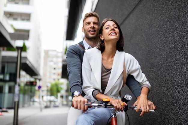 Красивая счастливая пара в любви на велосипеде в городе весело