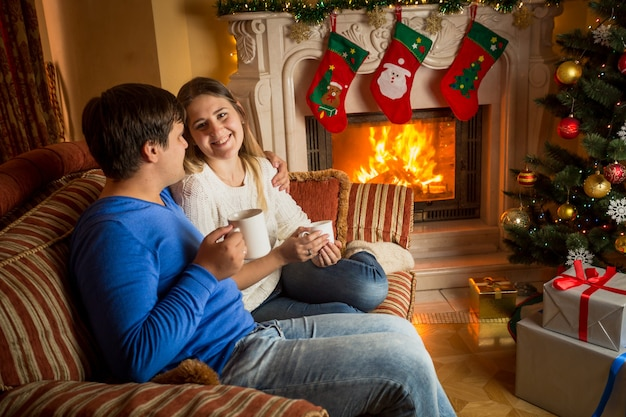 Beautiful happy couple in love drinking tea on sofa at burning fireplace decorated for christmas