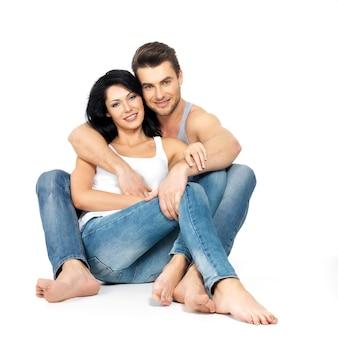 Belle coppie felici nell'amore su uno spazio bianco vestite in jeans blu e maglietta bianca