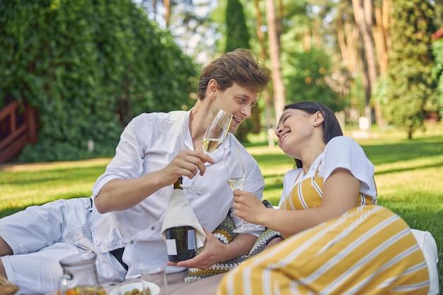 안경에 차가운 와인과 함께 피크닉에서 쉬고 아름다운 행복한 커플