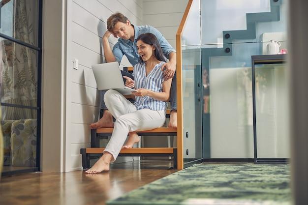 여자가 그녀의 남자 친구에게 노트북에 뭔가를 보여주는 동안 집에서 계단에 앉아 아름 다운 행복 한 커플
