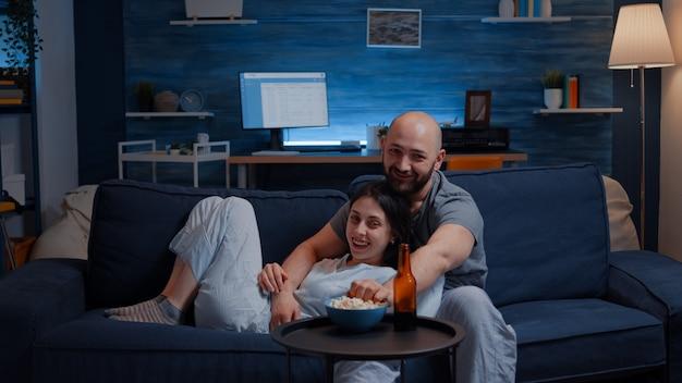 Bella coppia felice che guarda la tv sul divano rilassandosi di notte ridendo
