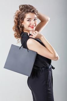 쇼핑 가방과 함께 전체적으로 우아한 블랙에 아름 다운 행복 곱슬 여자