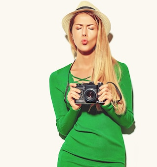 Beautiful happy cute blond woman girl in casual summer green hipster clothes takes photos holding retro photographic camera,  giving a kiss
