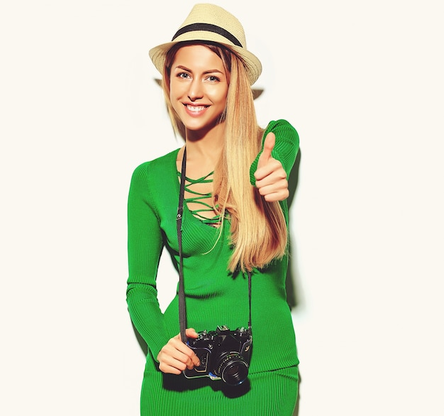 Beautiful happy cute blond woman girl in casual summer green hipster clothes takes photos holding retro photographic camera