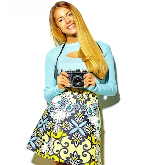 Beautiful happy cute blond woman girl in casual summer hipster clothes takes photos holding retro photographic camera