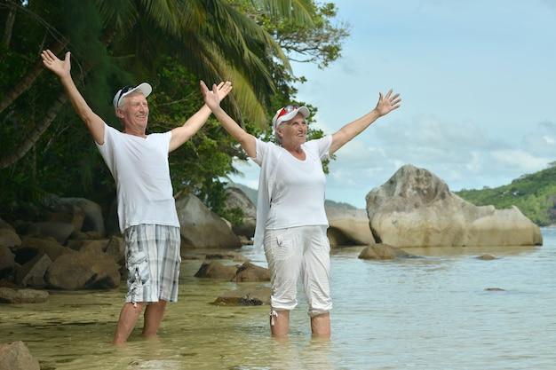 아름다운 행복한 노인 부부는 손을 들고 열대 리조트에서 휴식을 취합니다.