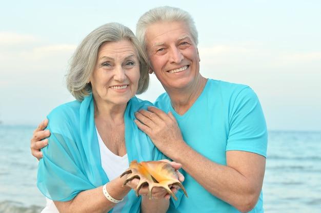아름다운 행복한 노인 부부는 껍질이 있는 열대 리조트에서 휴식을 취합니다.