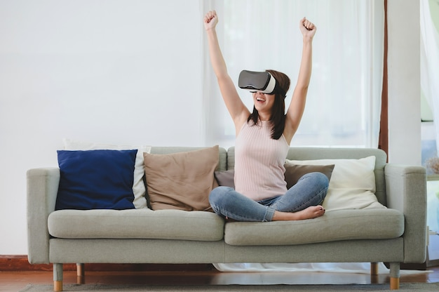 Beautiful happy excited asian woman in vr headset raising both hands up to celebrate wining or success in virtual reality at home