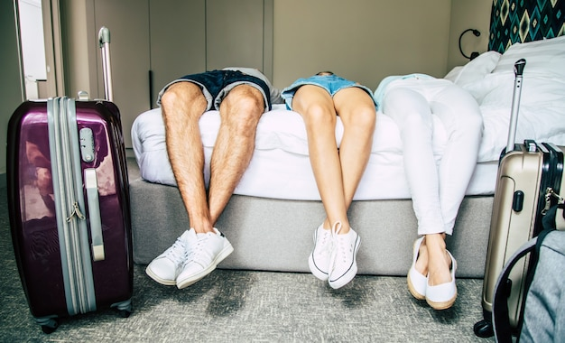 モダンなホテルのバックパックとスーツケースを持つ美しい幸せな興奮した家族