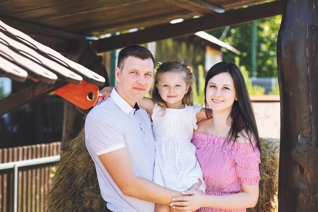Красивая счастливая семья, отец, мать и милая маленькая дочь на фоне сена на сельской ферме