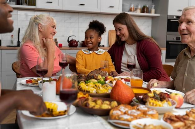 一緒に素敵な感謝祭のディナーを持っている美しい幸せな家族
