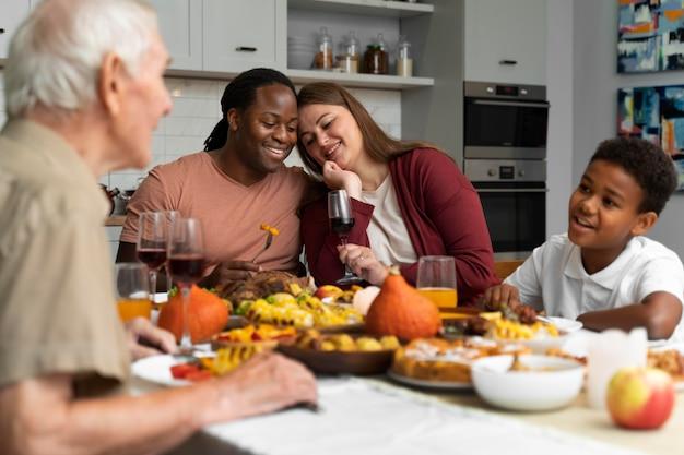 Красивая счастливая семья вместе обедает в честь дня благодарения
