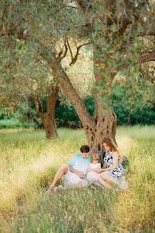 몬테네그로에서 나무 아래 앉아 올리브 과수원에서 아름 다운 행복 한 가족.