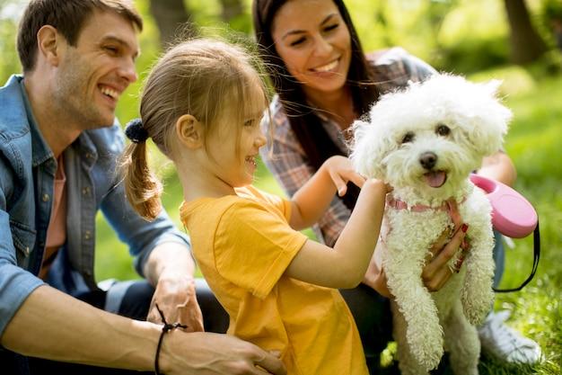 Красивая счастливая семья развлекается с собакой бишон на открытом воздухе