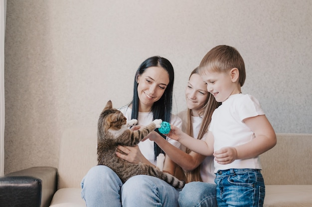 美しい幸せな家族のお母さんとソファに座って猫と遊んでいる2人の子供。