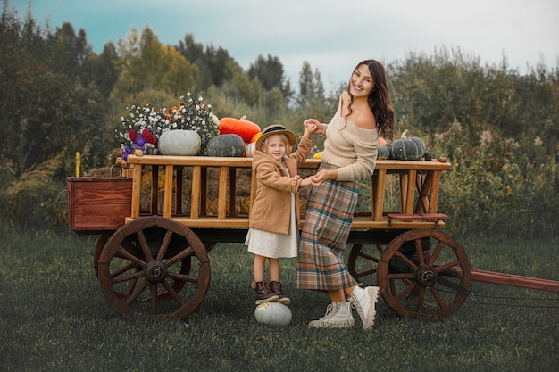 아름다운 행복한 가족 엄마와 딸이 화려한 호박이 든 나무 카트에 함께